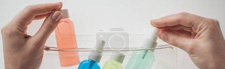Photo pour Plan panoramique de la femme mettant des bouteilles avec des liquides au sac cosmétique sur fond blanc - image libre de droit