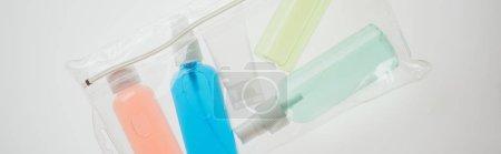 Photo pour Plan panoramique de sac cosmétique avec des bouteilles colorées avec des liquides sur fond blanc - image libre de droit