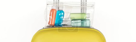 Photo for Panoramic shot of travel bag with cosmetic bag with colorful bottles with liquids isolated on white - Royalty Free Image