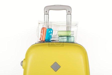 Foto de Bolsa de viaje con bolsa cosmética con botellas de colores con líquidos aislados en blanco. - Imagen libre de derechos