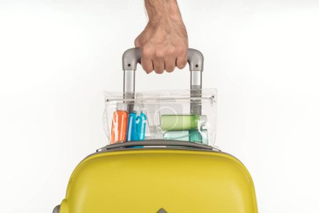 Photo for Cropped view of man holding travel bag with cosmetic bag with colorful bottles with liquids on white background - Royalty Free Image