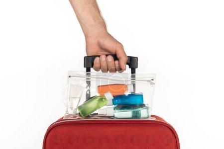 Photo pour Vue recadrée de l'homme tenant sac de voyage avec sac cosmétique avec des bouteilles colorées avec des liquides sur fond blanc - image libre de droit