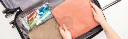 Photo for Panoramic shot of woman packing travel bag on white background - Royalty Free Image
