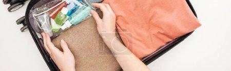 Photo pour Photo panoramique d'une femme emballant un sac de voyage sur fond blanc - image libre de droit