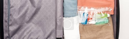 Photo for Panoramic shot of travel bag with towel, cosmetic bag with bottles, clothes - Royalty Free Image