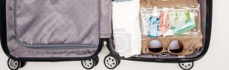 Photo pour Photo panoramique de sac de voyage avec serviette, sac cosmétique avec bouteilles, vêtements, lunettes de soleil sur fond blanc - image libre de droit