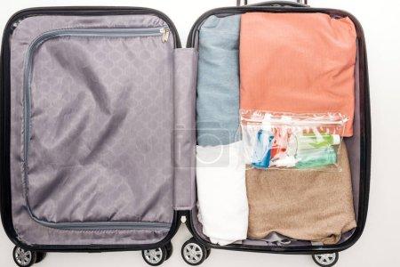 Photo pour Vue du dessus du sac de voyage avec serviette, sac cosmétique avec bouteilles, vêtements sur fond blanc - image libre de droit