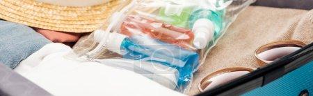 Panorama-Aufnahme von Reisetasche mit Handtuch, Kosmetiktasche mit Flaschen, Kleidung, Sonnenbrille