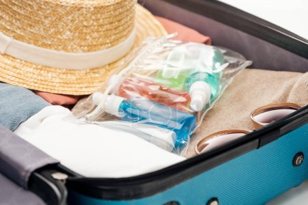 travel bag with towel, cosmetic bag with bottles, clothes, sunglasses and hat