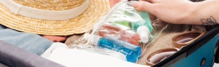 Photo for Panoramic shot of woman packing travel bag with cosmetic bag with bottles - Royalty Free Image