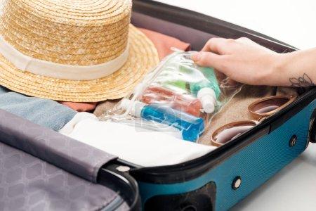 vista recortada de la mujer embalaje bolsa de viaje con bolsa de cosméticos con botellas