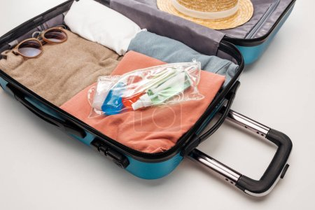 Photo for Travel bag with towel, cosmetic bag with bottles, clothes, sunglasses and hat - Royalty Free Image