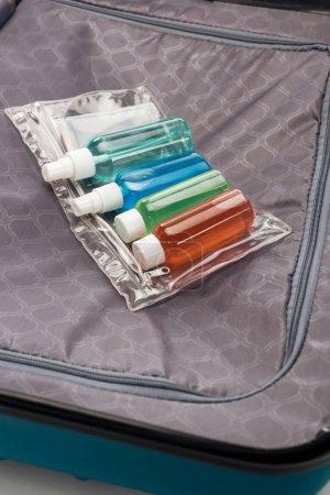 Photo pour Sac cosmétique transparent avec des bouteilles colorées sur le sac de voyage - image libre de droit