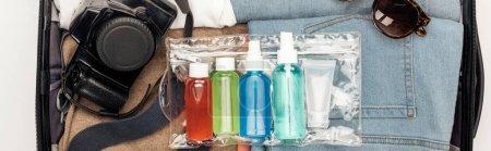 Photo pour Photo panoramique de sac de voyage avec serviette, sac cosmétique avec des bouteilles colorées, appareil photo numérique, vêtements et lunettes de soleil - image libre de droit