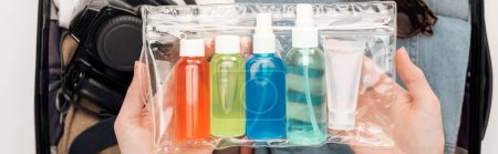Photo for Panoramic shot of woman packing travel bag with cosmetic bag with colorful bottles - Royalty Free Image