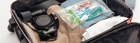 Foto de Foto panorámica de bolsa de viaje con toalla, bolsa cosmética con botellas de colores, cámara digital, ropa. - Imagen libre de derechos