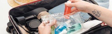 Photo pour Plan panoramique de sac de voyage femme emballage avec sac cosmétique avec des bouteilles colorées - image libre de droit