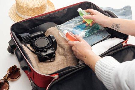 Photo pour Vue recadrée de sac de voyage femme emballage avec sac cosmétique avec des bouteilles colorées - image libre de droit