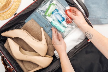 Photo for Cropped view of woman packing travel bag with cosmetic bag with colorful bottles - Royalty Free Image