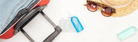Photo pour Photo panoramique d'un sac de voyage, d'un chapeau, de lunettes de soleil, de bouteilles de liquides et de vêtements sur fond blanc - image libre de droit