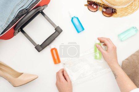 vista recortada de la mujer sosteniendo bolsa de cosméticos con botellas de colores sobre fondo blanco tatuado