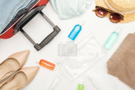 Photo for Top view of travel bag, hat, sunglasses, cosmetic bag with bottles with liquids, clothes, towel, heels - Royalty Free Image