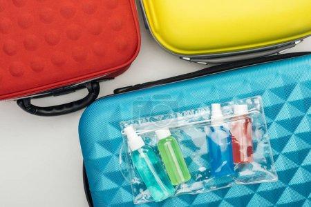 Photo pour Vue du dessus du sac cosmétique et des bouteilles avec des liquides sur le sac de voyage - image libre de droit