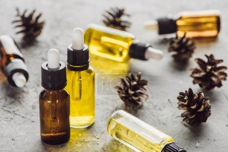 Photo pour Mise au point sélective des bouteilles à huile naturelle près des cônes secs sur une surface de pierre grise - image libre de droit
