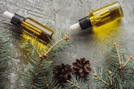 top view of bottles with natural oil near fir branches and dry cones on grey stone surface
