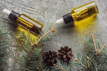 Photo pour Vue du haut des bouteilles avec huile naturelle près des branches de sapin et cônes secs sur une surface de pierre grise - image libre de droit