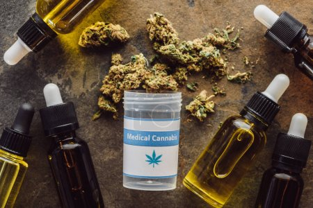 Photo pour Top view of medical marijuana buds near container and bottles with hemp oil on marble surface - image libre de droit