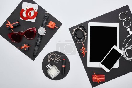 Foto de Vista superior de gadgets, cajas de regalo, gafas de sol, perfume, reloj de pulsera, pendientes, auriculares, pulseras, lápiz de labios. - Imagen libre de derechos
