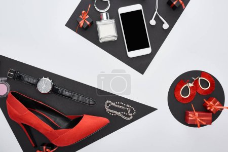 Photo for Top view of gadget, gift boxes, perfume, bracelets, blush, earrings, earphones, wristwatch, shoes - Royalty Free Image