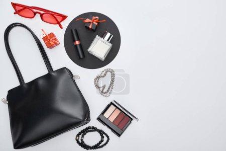 Photo pour Vue du haut du sac, coffrets cadeaux, parfum, bracelets, cosmétiques décoratifs, lunettes de soleil - image libre de droit