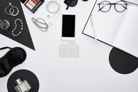 Photo for Top view of gadget, perfume, bracelets, decorative cosmetics, sleeping mask, earphones, glasses, notebook, earrings - Royalty Free Image