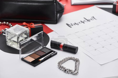Photo for Selective focus of calendar with lettering november, bag, gift, bracelets, eye shadow, perfume, lipstick - Royalty Free Image