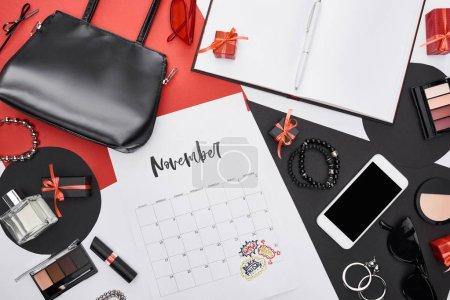 Photo pour Haut de page du calendrier avec lettres novembre, gadget, boîtes à cadeaux, parfum, bracelets, cosmétiques décoratifs, sac, lunettes de soleil, boucles d'oreilles, lunettes de soleil - image libre de droit
