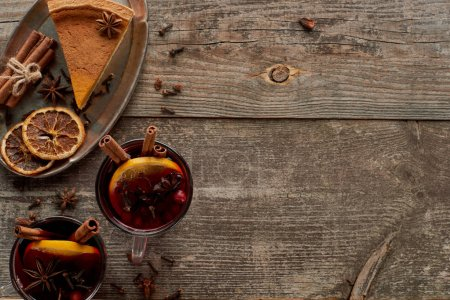 Photo for Top view of piece of pie and red spiced mulled wine with berries, anise, orange slices and cinnamon on wooden rustic table - Royalty Free Image