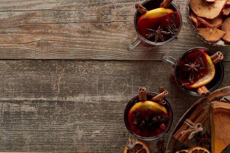 Photo pour Vue du dessus du morceau de tarte et du vin chaud épicé rouge aux baies, à l'anis, aux tranches d'orange et à la cannelle sur une table rustique en bois - image libre de droit