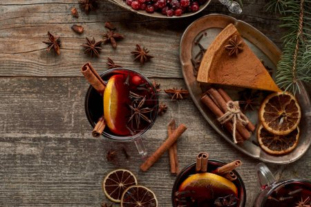 Photo pour Top view of red spiced mulled wine near fir branch, pie, berries, anise, orange slices and cinnamon on wooden rustic table. - image libre de droit