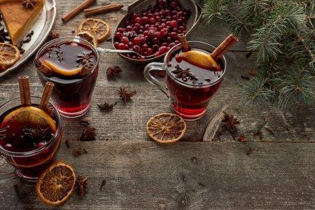 Photo pour Vin mousseux épicé rouge près de la branche de sapin, baies, anis, tranches d'orange et cannelle sur table rustique en bois - image libre de droit