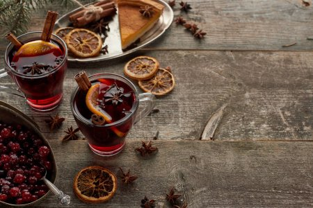 red spiced mulled wine near berries, anise, orange slices and cinnamon on wooden rustic table with copy space