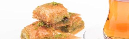 Photo pour Délicieuse baklava turkish et thé isolés sur pellicule blanche panoramique - image libre de droit