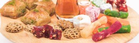 Photo pour Planche en bois avec de délicieuses sucreries turkish et thé isolés sur fond blanc, plan panoramique - image libre de droit