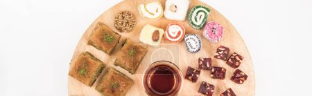 Photo for Top view of wooden board with delicious turkish sweets and tea isolated on white, panoramic shot - Royalty Free Image
