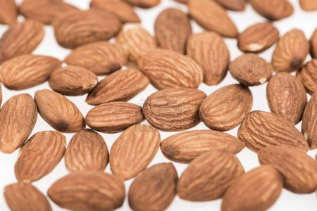 Photo for Almond nuts scattered isolated on white - Royalty Free Image