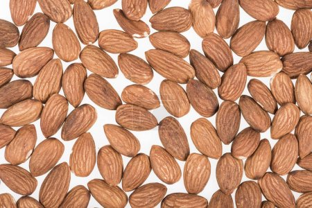 Photo for Top view of almond nuts scattered isolated on white - Royalty Free Image