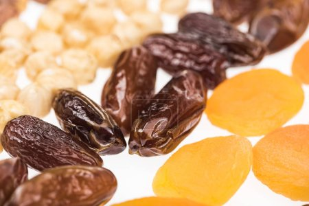 Photo for Close up view of dried apricots, dates and hazelnut isolated on white - Royalty Free Image
