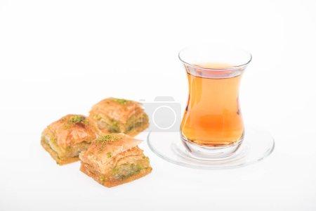 Photo pour Tasse de thé près de baklava turkish isolée sur blanc - image libre de droit