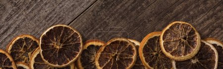 panoramic shot of dried orange slices on wooden background